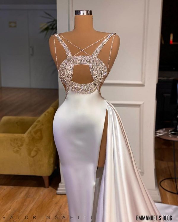 This custom made dress is ideal for a bride who wants to feel elegant on her wedding day. This is a fashion statement made of white satin material beaded with pearls in an artistic formation. This outfit is every bride's prayer as it shows off the dashing figure of the wearer hence suitable for all body sizes. This dress could be a wedding dress( great civil wedding), reception dress or also worn to the red carpet. The perfect jewellery/ accessory to go with this is vintage white pearl or Glittering diamond for necklace, bracelets and earrings. The headpiece is optional (tulle inspired headpiece). The ideal choice would be a low-set bun or Sleek ponytail For the makeup, bronzed eyes with bold lippy will complete this outfit. For the shoes, a pair of Christian Louboutin patent leather Sandal will do. This luxury dress will be perfect for an English themed wedding